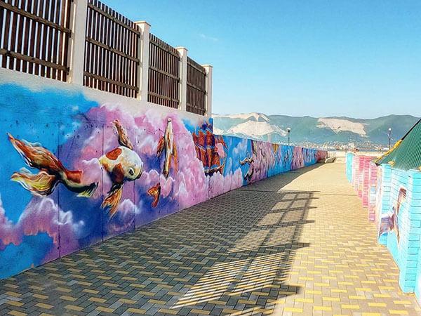 В Новороссийске около моря нарисовали граффити с рыбами в розовых облаках